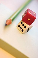Close-up of two dices with a pencil