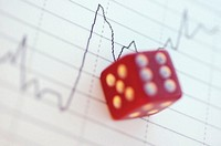 Close-up of a dice over a line graph