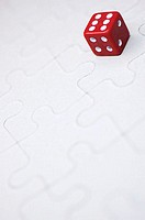 Close-up of a dice on a jigsaw puzzle