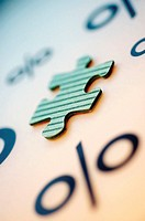 Close-up of a jigsaw piece and a percentage sign