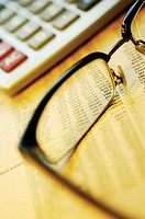 Close-up of eyeglasses and a calculator on a financial newspaper