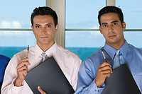 Portrait of two businessmen holding pens