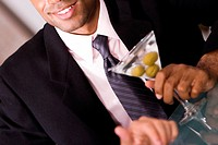 Close-up of a businessman holding a martini glass