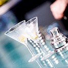 Close-up of two martini glasses and a cocktail shaker on a bar counter