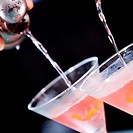 Close-up of a person's hand pouring martini into martini glasses