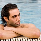Close-up of a mid adult man leaning at the edge of a swimming pool