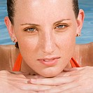 Portrait of a young woman leaning at the edge of a swimming pool