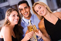 Two young women and a young man toasting with champagne flutes