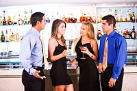 Two mid adult men and two young women standing in a bar