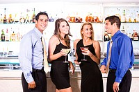 Two mid adult men and two mid adult women standing in a bar