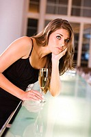 Young woman leaning over a bar counter holding a champagne flute