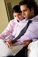 Businessman and a businesswoman in front of a laptop