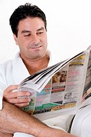 Close-up of a mid adult man reading a newspaper