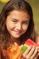 Portrait of a girl holding a slice of watermelon