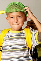 Portrait of a boy holding a fishing net over his head