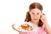 Portrait of a girl holding a donut in a plate with cream on the tip of her finger