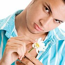Portrait of a young man holding a flower