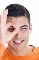 Portrait of a mid adult man making an ok sign in front of his eye