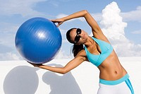 Young woman exercising with a fitness ball (thumbnail)