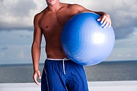 Mid section view of a man holding a fitness ball