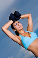 Low angle view of a young woman wearing boxing gloves (thumbnail)