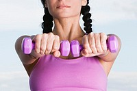 Close-up of a young woman holding dumbbells