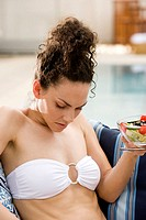 Close-up of a young woman holding a bowl of fruit salad