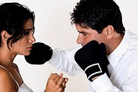 Side profile of a mid adult man punching a young woman