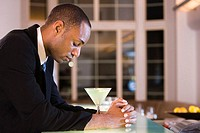 Side profile of a businessman with a glass of martini