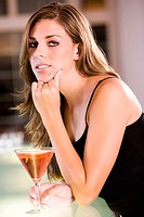 Portrait of a young woman leaning over a bar counter