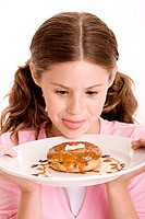 Close-up of a girl holding a donut in a plate licking her lips