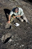 Early human footprints. Researcher Marco Avanzini measuring fossilized footprints in volcanic rock on the Roccamonfina volcano, near Naples, Italy. Kn...