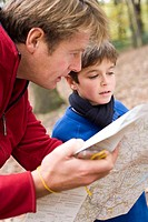 Father and son reading a map. The father is holding a compass in his right hand. A compass can be used together with a map to travel in the correct di...
