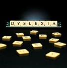 Dyslexia. Scrabble letters spelling the word dyslexia, with other scrabble letters in the foreground. Dyslexia is a congenital and developmental disor...