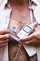 Portable heart monitor. Man holding a portable electrocardiograph that is worn on a strap around the neck. The wires lead to electrodes attached to hi...