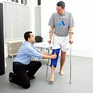 Physiotherapy. Physiotherapist assessing the mobility in a patient´s knee. The patient is wearing a brace to immobilise his leg after an injury. Physi...