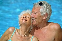 Close_up of senior couple romancing at poolside