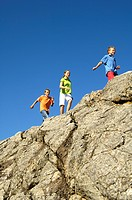 Low angle view of three children walking on cliff