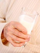 Drinking milk. Glass of milk in the hand of an elderly woman. Milk is a good source of calcium. A high calcium intake can help prevent the development...