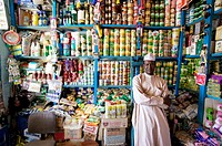 Shopkeeper in his store surrounded by packaged food products. Photographed in Chad.