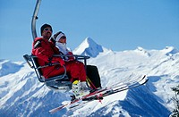 Two people traveling on a ski lift