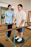 Rehabilitation session in hospital gym with patient working on balance with physiotherapy assistant