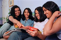 Group of teenage girls sitting on sofa reading magazine,