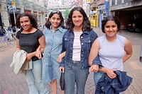 Group of teenage girls in town on shopping trip, walking with linked arms,