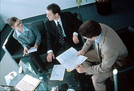 High angle view of businesswoman and two businessmen discussing in meeting