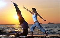 Side profile of two young women doing yoga on beach
