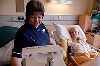 Nurse with disability taking patient´s blood pressure on hospital ward,