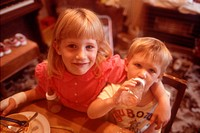 Young girl sitting at table with arm around younger brother who is drinking from feeding bottle,