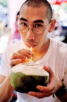 Man drinking coconut milk. Jatujak market. Bangkok, Thailand.