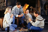 Two couples sitting by fireplace, playing card game